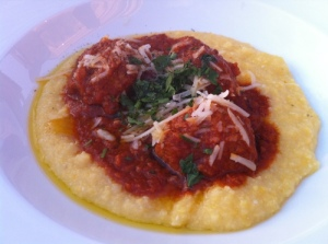 Two housemade meatballs in marinara over creamy polenta, pine nuts, currants, grana padano.
