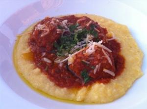 Two housemade meatballs in marinara over creamy polenta, pine nuts, currants, grana padano.