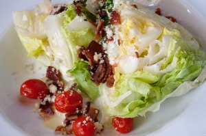 Fun iceberg wedge salad with tomatoes, bacon, green onions and blue cheese.