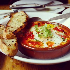 Huevos a la flamenco, baked eggs with chorizo, peppers, tomato sauce, and bechamel.