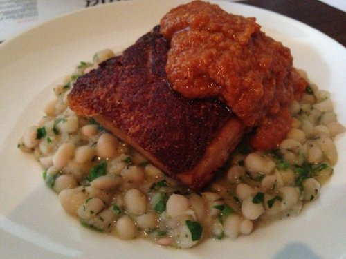 Crispy skinned pork belly with romesco sauce and beans.