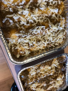 Two sheet pans of chicken enchiladas and another of just enchilada sauce.